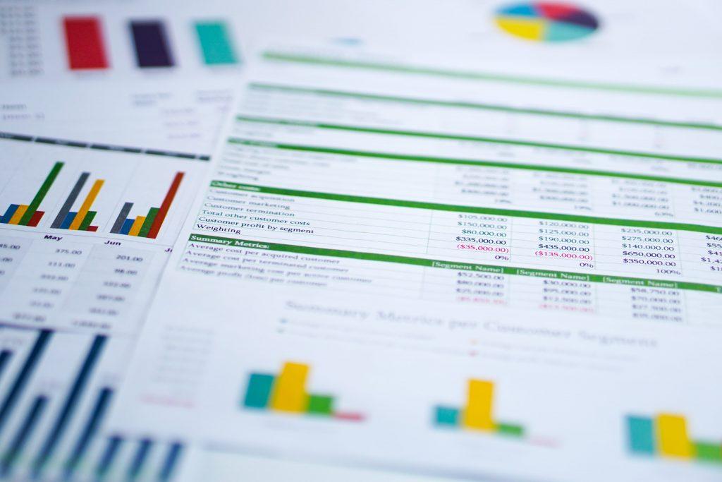 Mehrere übereinanderliegende Seiten mit farbigen Tabellen und Diagrammen darauf