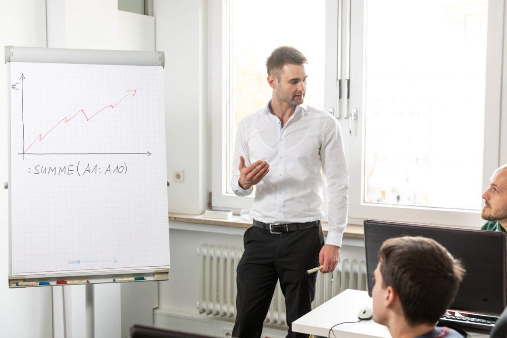 Jan Trummel am Flipchart und erklärt zwei Seminarteilnehmern etwas in Excel.
