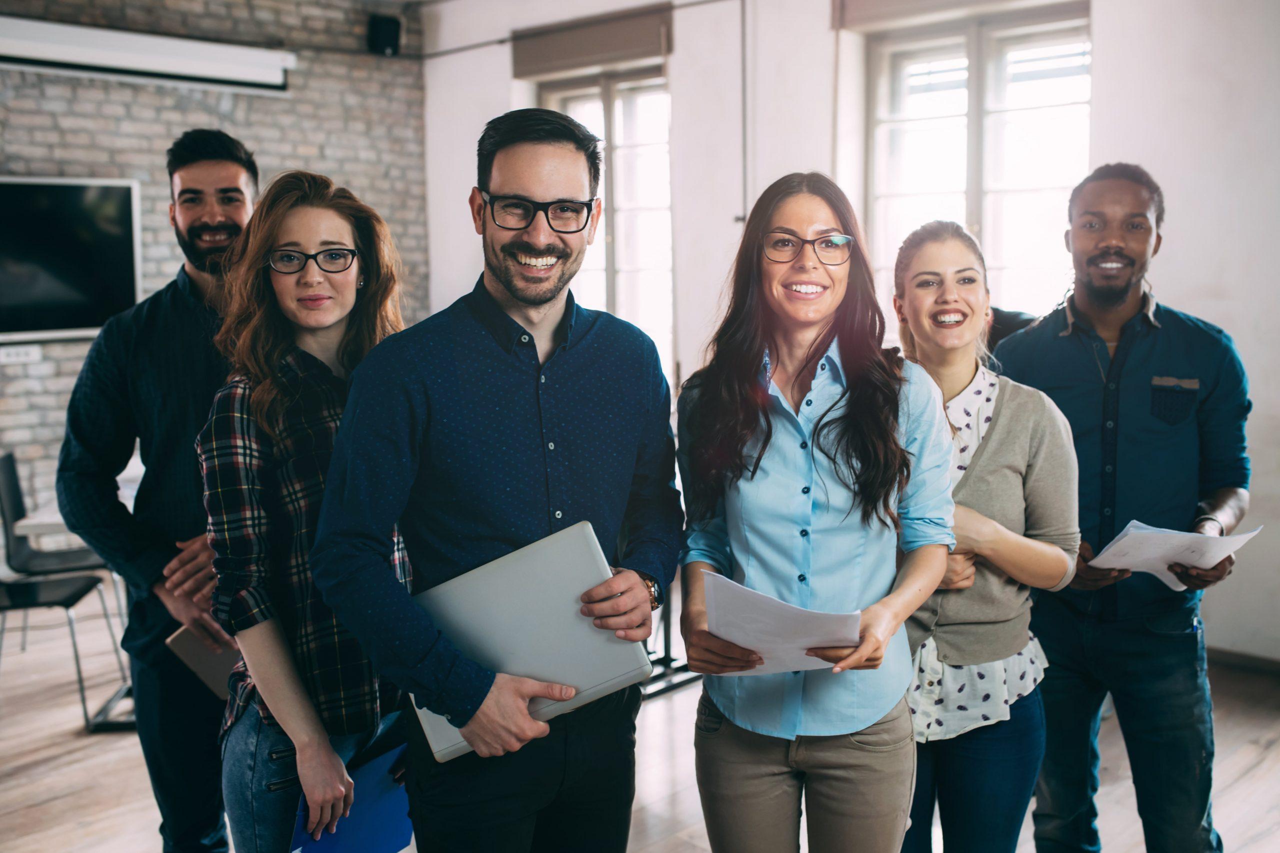 6 Geschäftsleute mit Laptops in der Hand stehen im Halbkreis