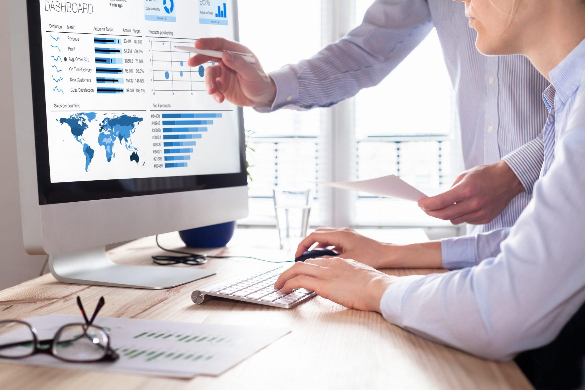 Team von Finanzexperten, die auf dem Computerbildschirm ein Dashboard für Geschäftsanalytik (BA) oder Intelligence (BI) diskutieren, in dem die Umsatzdaten und Betriebsdaten sowie die wichtigsten Leistungsindikatoren (KPI) dargestellt werden