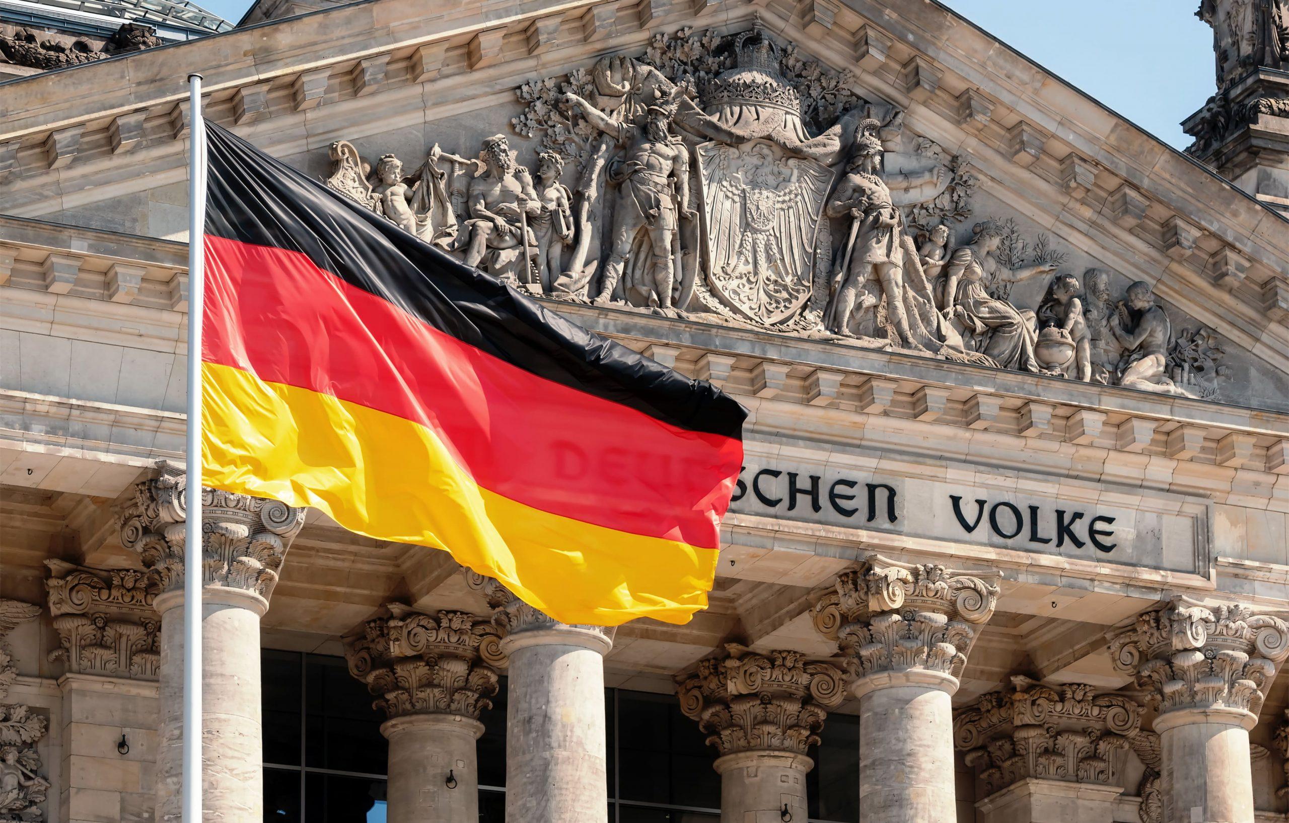 Der Reichstag mit einer wehenden deutschen Flagge davor. Ein Teil des Textes über dem Eingang ist von der Fahne verdeckt.